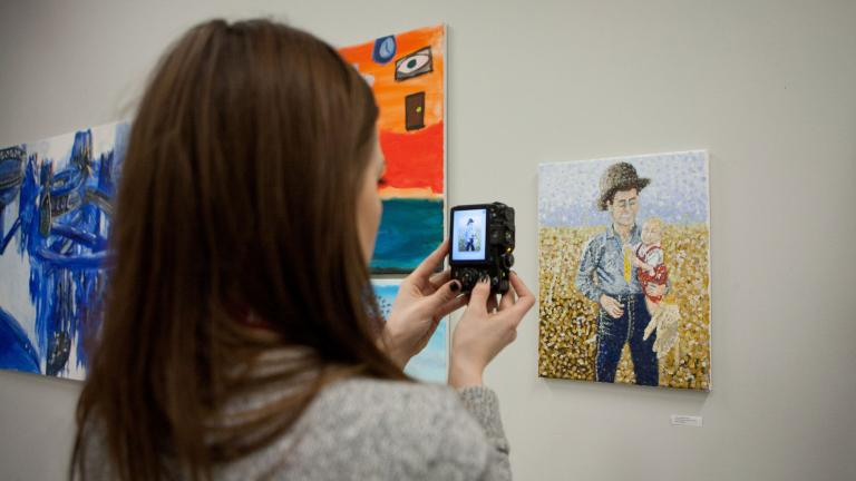 Student taking a photo of artwork displayed at the Art and Creativity Exhibition event